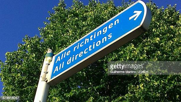Low Angle View Of Sign Board Against Tree