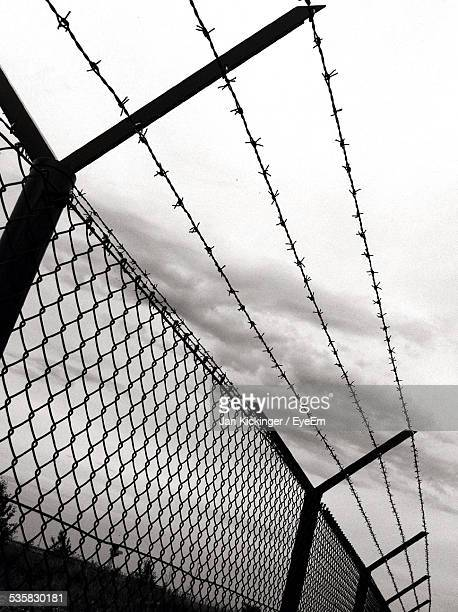 Low Angle View Of Silhouette Barbed Wire Against Sky At Dusk