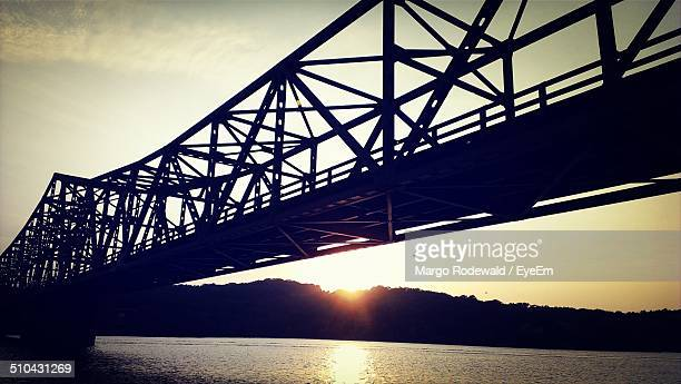 Low angle view of silhouette bridge over water at sunset
