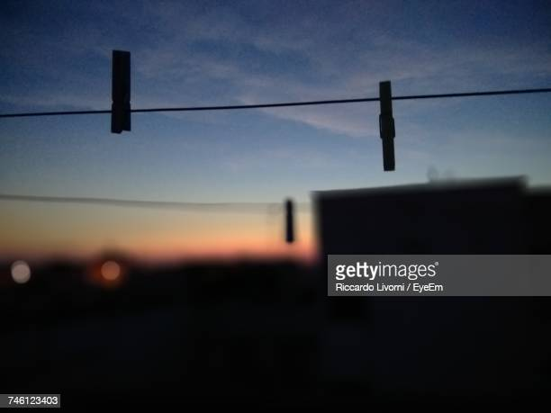 Low Angle View Of Silhouette Clothespin On Rope Against Sky During Sunset