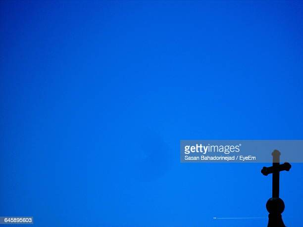 Low Angle View Of Silhouette Cross Against Clear Blue Sky On Sunny Day