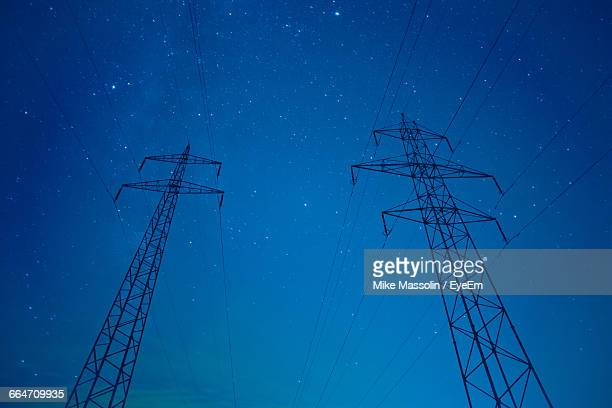 Low Angle View Of Silhouette Electricity Pylons Against Star Field At Night