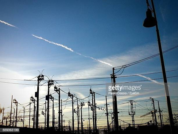 Low Angle View Of Silhouette Electricity Pylons At Sunset