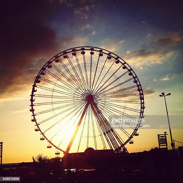 Low Angle View Of Silhouette Ferris Wheel At Sunset