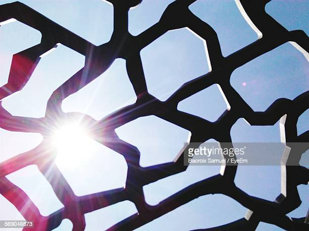 Low Angle View Of Silhouette Geometric Shapes Against Sky With Sunlight