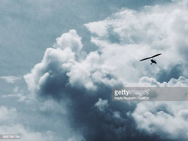 Low Angle View Of Silhouette Hang Glider Against Cloudy Sky