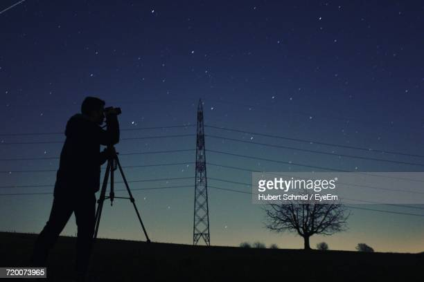 Low Angle View Of Silhouette Man Photographing Electricity Pylon Against Star Field At Night