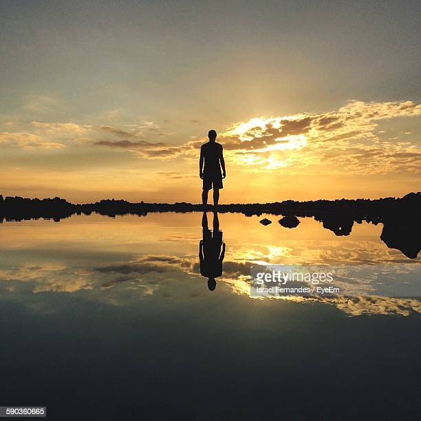 Low Angle View Of Silhouette Man Standing In Shallow Water At Beach