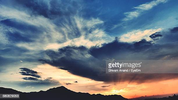Low Angle View Of Silhouette Mountain Against Cloudy Sky During Sunset