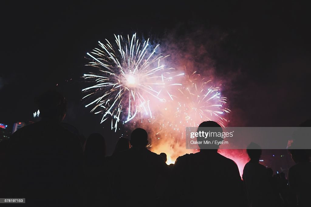 Low Angle View Of Silhouette People Looking At Firework Display At Night