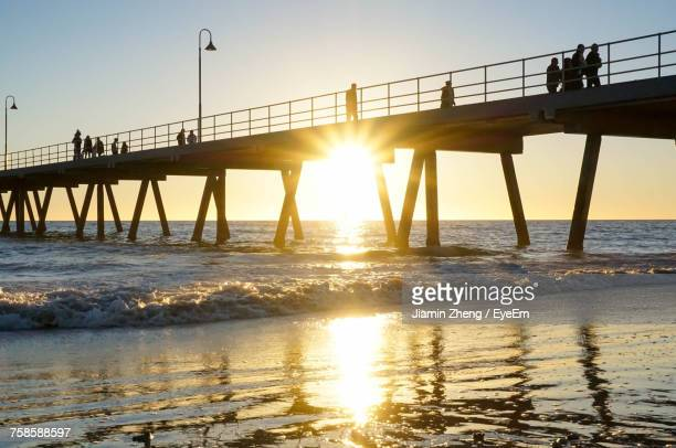 Low Angle View Of Silhouette People Walking On Pier Over Sea At Glenelg Beach During Sunset