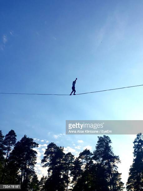 Low Angle View Of Silhouette Person Tightrope Walking