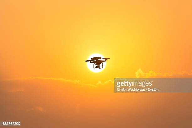 Low Angle View Of Silhouette Quadcopter Flying In Orange Sky
