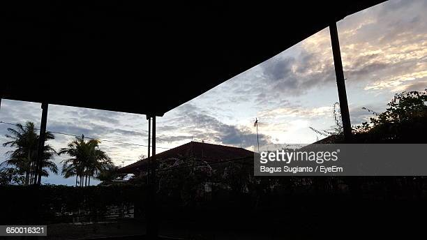 Low Angle View Of Silhouette Roof And Houses Against Cloudy Sky At Sunset