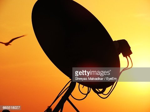 Low Angle View Of Silhouette Satellite Dish Against Orange Sky
