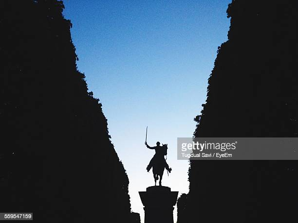 Low Angle View Of Silhouette Statue Amidst Mountains Against Clear Sky