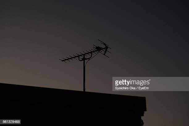 Low Angle View Of Silhouette Television Aerial On Roof At Dusk