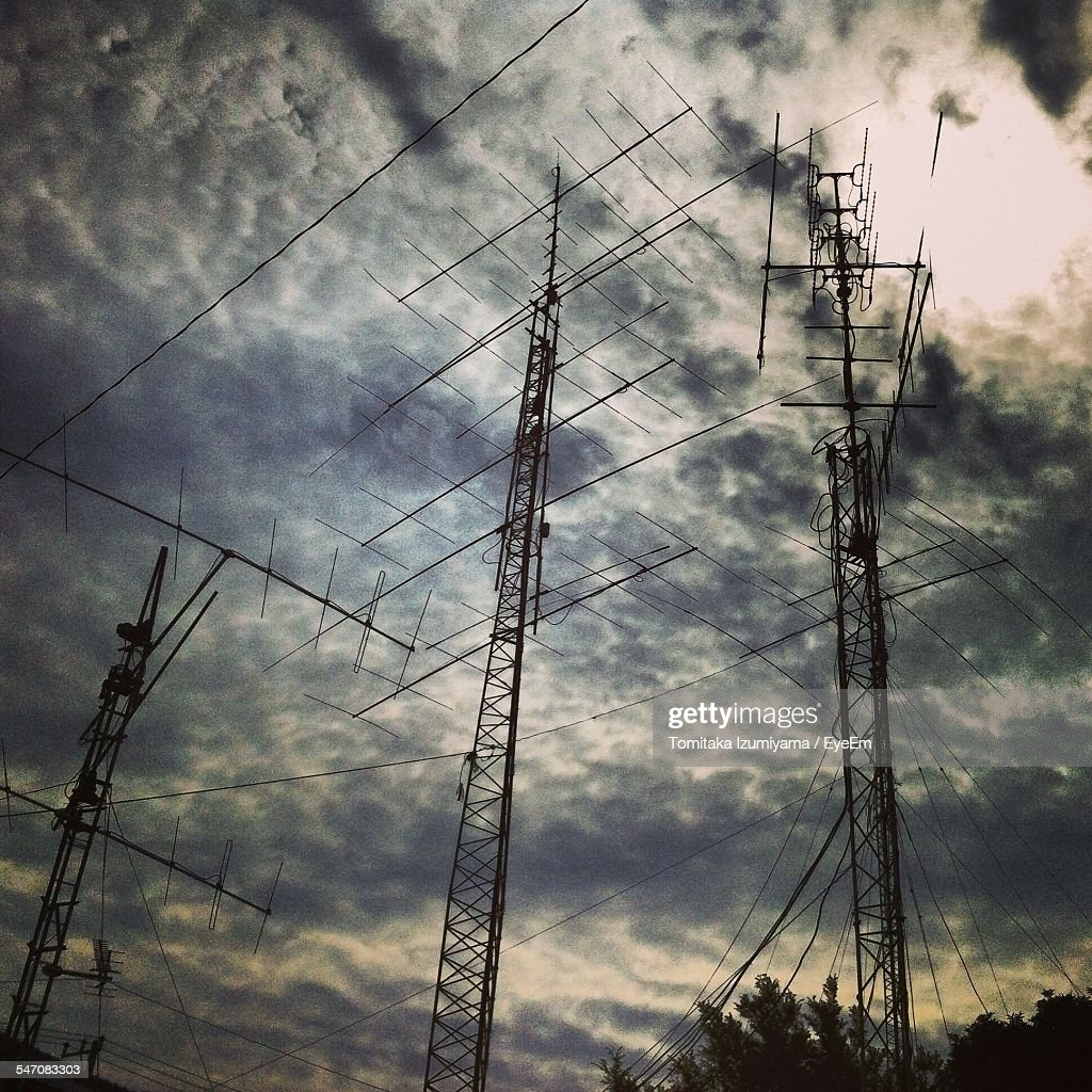 Low Angle View Of Silhouette Transmission Towers Against Cloudy Sky At Dusk