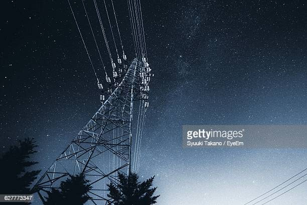 Low Angle View Of Silhouette Trees By Electricity Pylon Against Star Field At Night