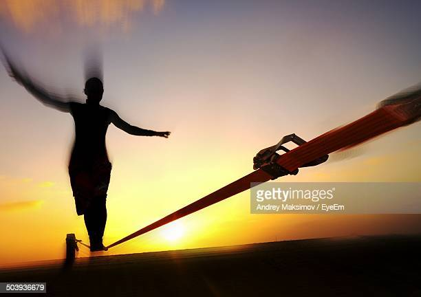 Low angle view of silhouette woman walking on rope at sunset