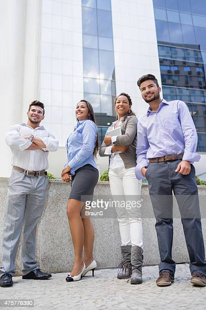 Low angle view of smiling business team outdoors.