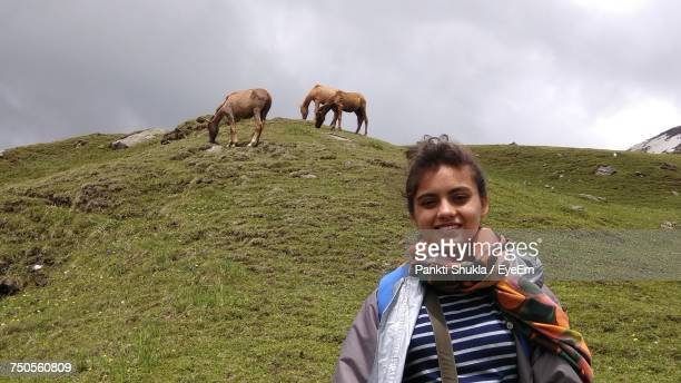 Low Angle View Of Smiling Woman With Horses In Background