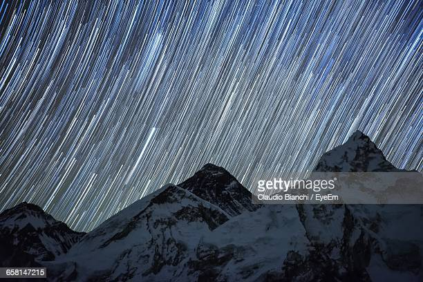 Low Angle View Of Snow Covered Mountains Against Star Trails