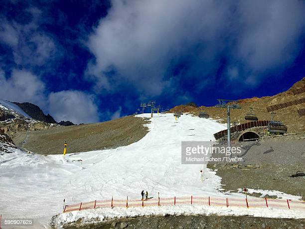 Low Angle View Of Snow Covered Pathway On Mountain Against Cloudy Sky