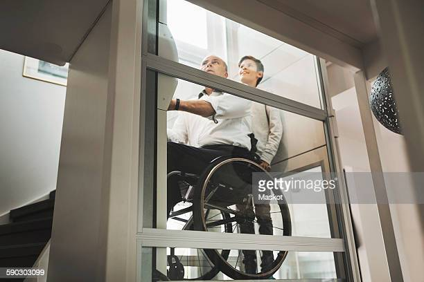 Low angle view of son and father in wheelchair lift at home