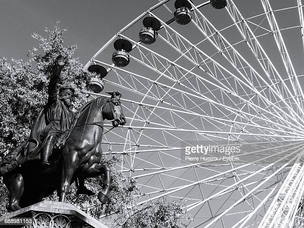 Low Angle View Of Statue By Ferris Wheel Against Sky