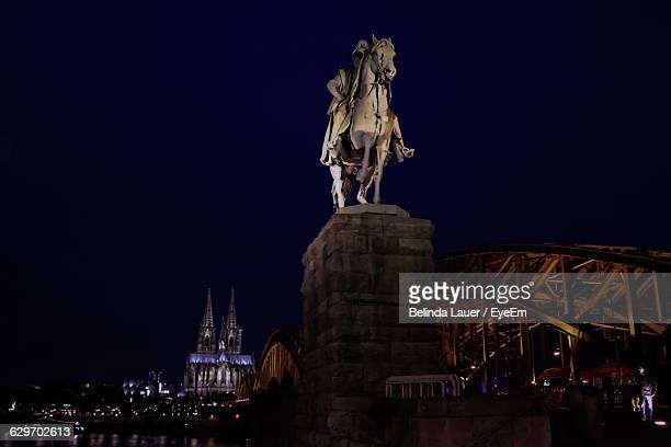 Low Angle View Of Statue By Hohenzollernbrucke Against Sky At Night