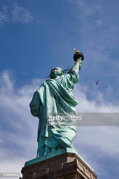 Low angle view of Statue of Liberty and airplane in blue sky, New York city, USA