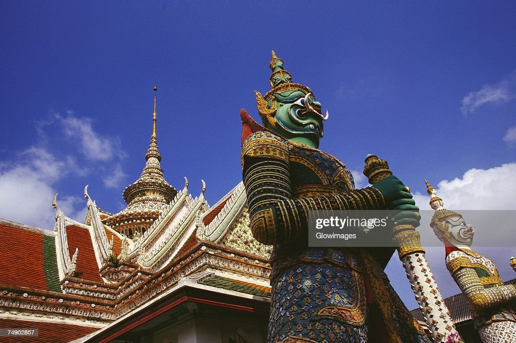 Low angle view of statues in front of a temple, Wat Arun, Bangkok, Thailand : Stock Photo