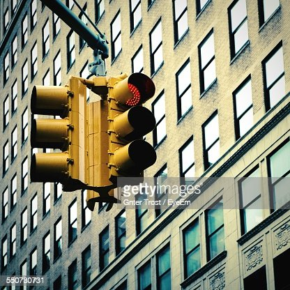 Low Angle View Of Stoplights Against Building In City