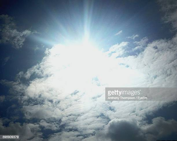 Low Angle View Of Sun Hiding Behind Clouds