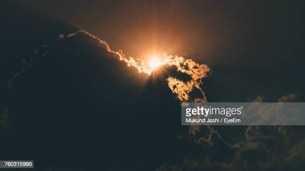 Low Angle View Of Sunlight Streaming Through Cloudy Sky During Sunset