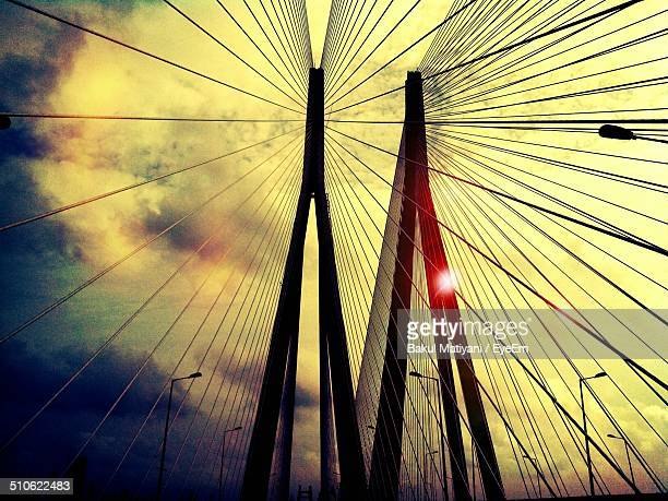 Low angle view of suspension bridge cables against clouds