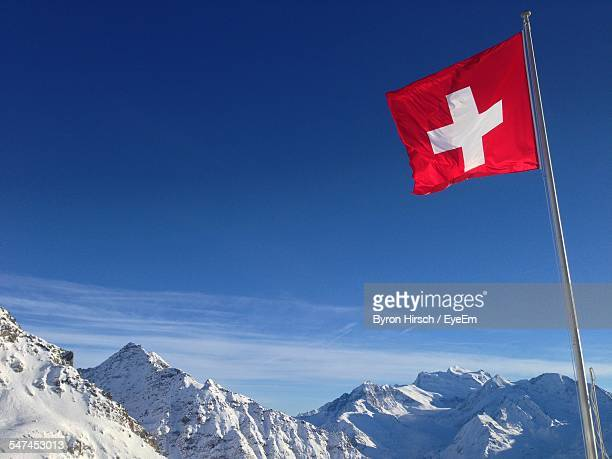Low Angle View Of Swiss Flag Against Blue Sky