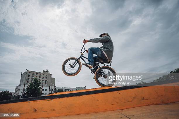 Low angle view of teenage boy performing stunt on ramp against cloudy sky
