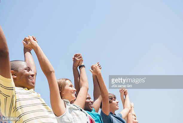 Low angle view of teenagers holding hands under blue sky