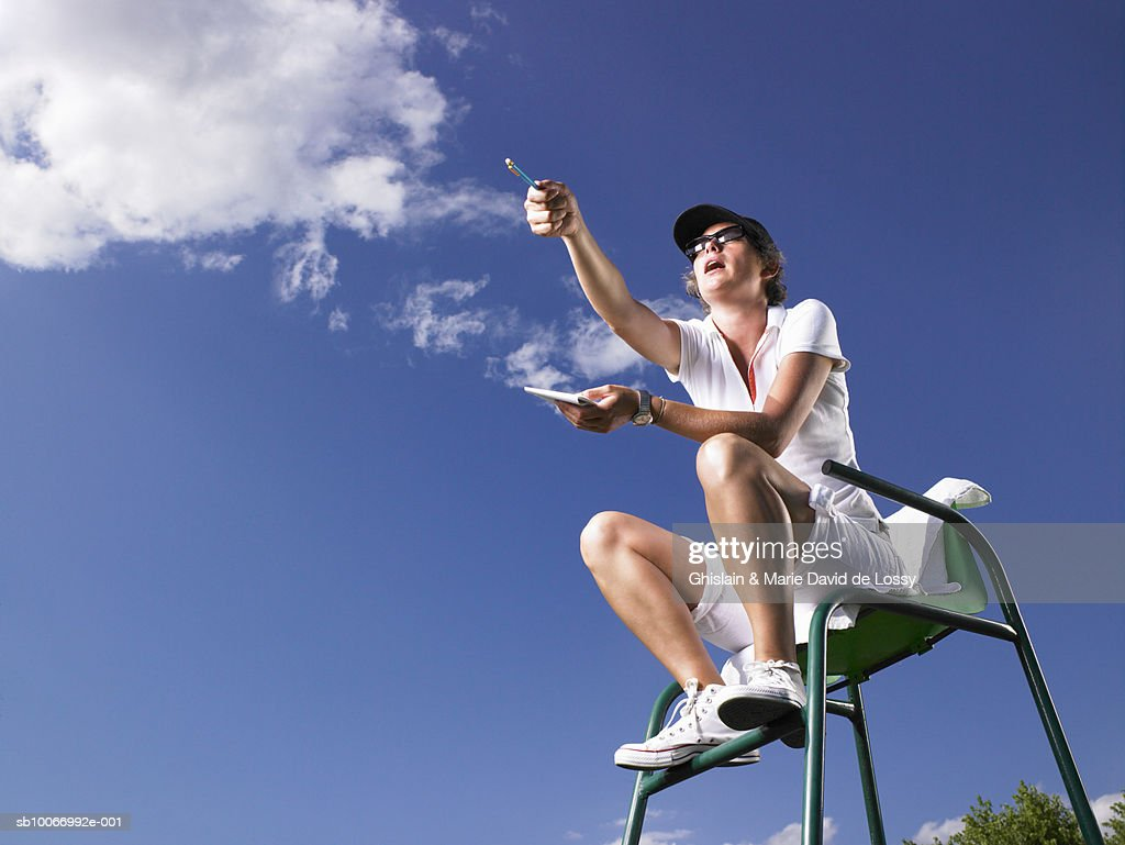 Low angle view of tennis umpire sitting in chair, pointing : Stock Photo