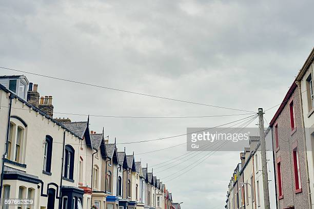 Low angle view of terraced houses with telegraph pole and wires, Maryport, Cumbria, UK
