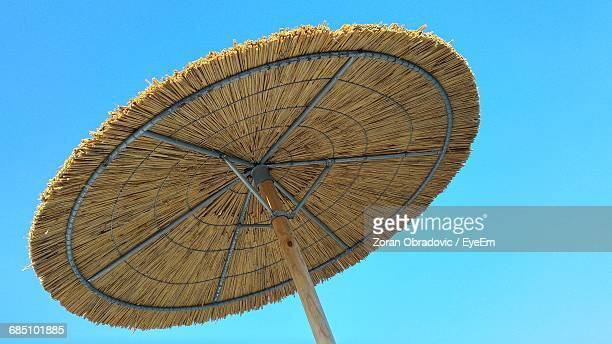 Low Angle View Of Thatched Roof Parasol Against Clear Blue Sky