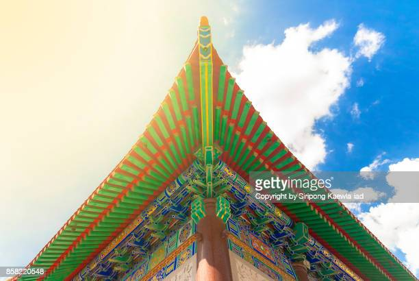 Low angle view of the Chinese style roof and the decoration outside the Chinese temple in Thailand.