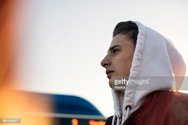 Low angle view of thoughtful teenager wearing hooded shirt standing against clear sky