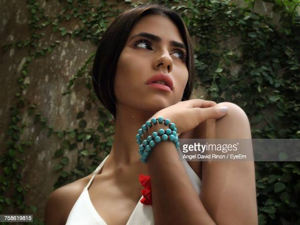 Low Angle View Of Thoughtful Woman Looking Away Against Creeper Plants On Wall