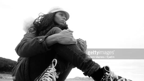 Low Angle View Of Thoughtful Woman Sitting Against Clear Sky