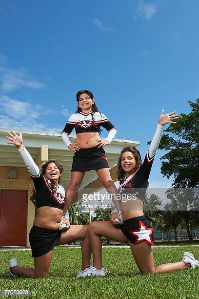 Low angle view of three cheerleaders balancing in a lawn