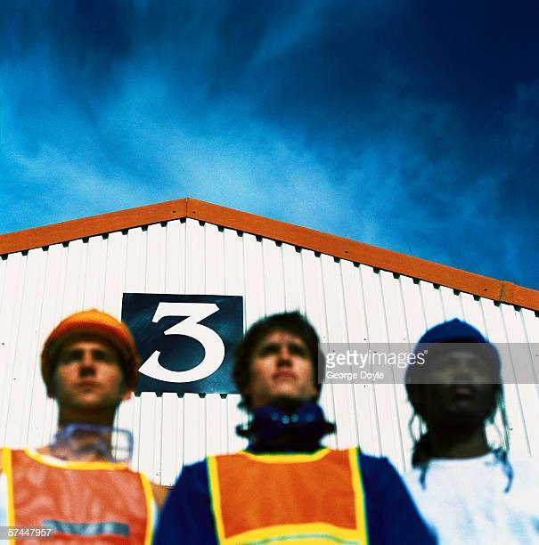 low angle view of three construction workers standing in front of a metal shed (blurred)