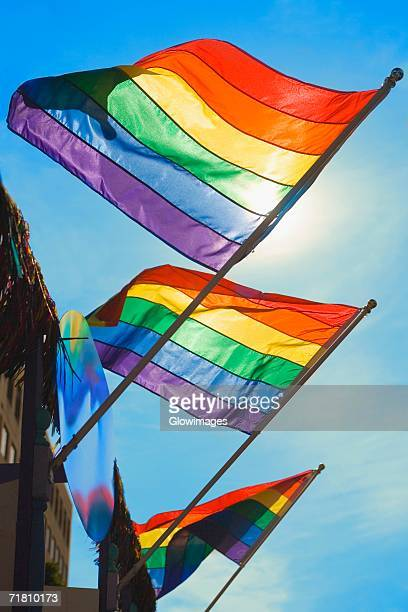 Low angle view of three gay pride flags fluttering on a building